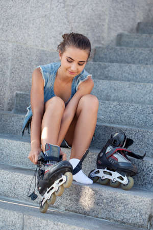 rollerblading: beautiful smiling girl sitting on the stairs and puts on skates