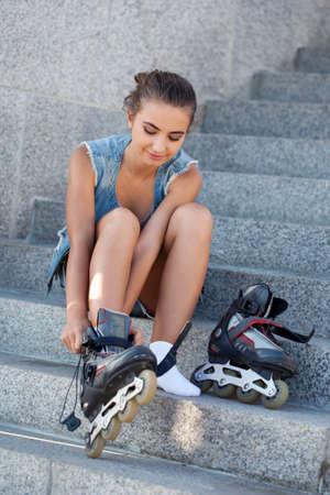 rollerblading: hermosa muchacha sonriente sentada en las escaleras y se pone los patines Foto de archivo