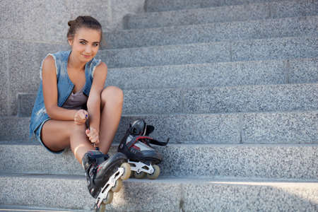 rollerblading: beautiful smiling girl sitting on the stairs and puts on skates and looking at camera