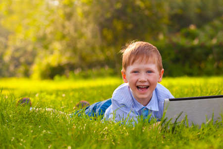 boy laying on green grass in the park with laptop photo