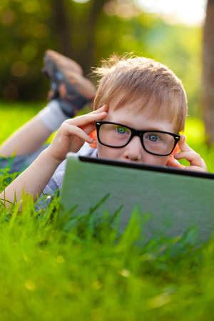 funny little boy looking from behind laptop in the park photo