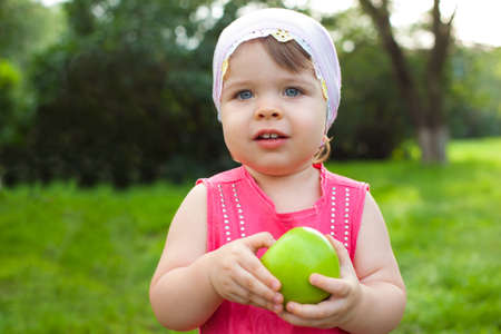 cute little girl walking in the park with green apple photo