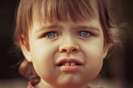 niños tristes: closeup retrato de la cara pequeña niña al aire libre