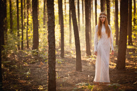 fairy woman wearing long dress walking at forest photo