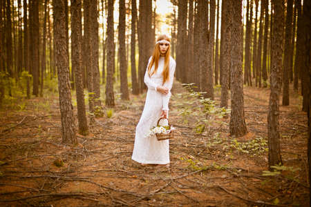 beautiful woman standing in the woods and holding a basket with daisies photo