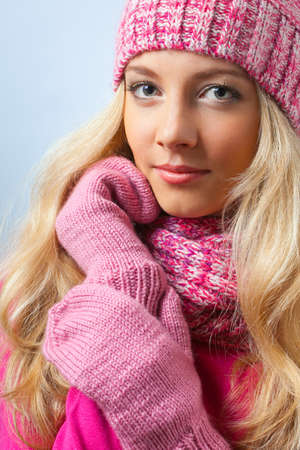 beautiful blonde woman wearing knitwear over blue photo