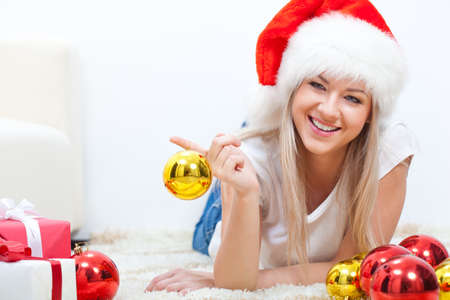 among: happy woman in santa hat laying on carpet among gifts and balls, holding ball on finger