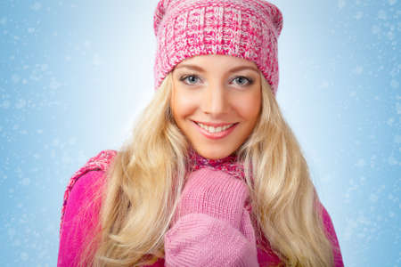 happy beautiful blonde woman wearing pink knitwear over blue background with snow photo