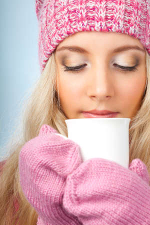 sweater girl: beautiful blonde woman holding white cup of drink over blue