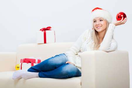 smiling woman wearing santa hat sitting on sofa photo