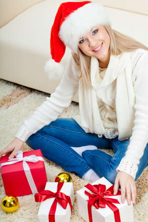 happy blonde woman wearing santa hat sitting on the floor with gifts, top point of view photo