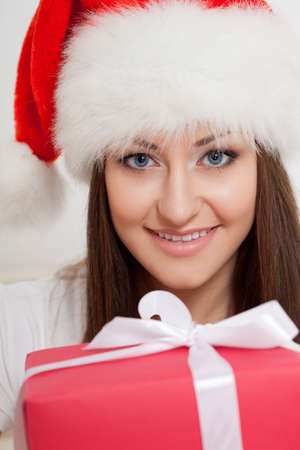 brunette woman wearing santa hat holding red gift box photo