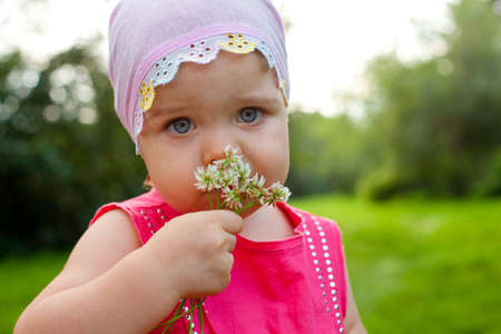 little girl holding bunch of clover outdoors and looking at camera photo