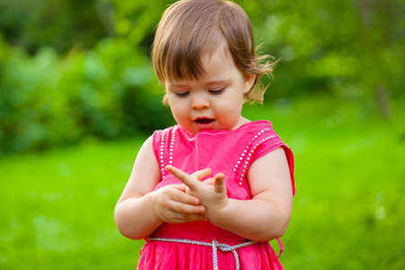 little girl counting her fingers in the park Stock Photo