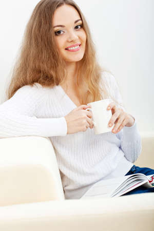 brunette  woman sitting on the sofa with white cup and reading the book Stock Photo - 16466489