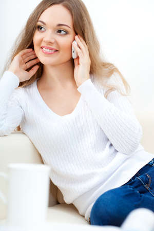 brunette woman sitting on sofa and talking by phone Stock Photo - 16466493