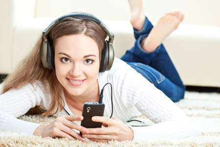 attractive gorgeous: brunette woman lying on carpet and listening to music, looking at camera Stock Photo