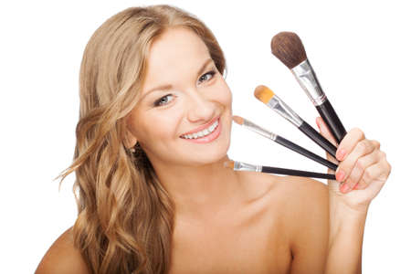 smiling blonde woman holding set of cosmetic brushes photo