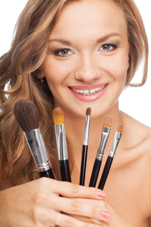 closeup happy blonde woman holding set of cosmetic brushes photo