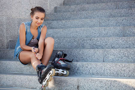 beautiful smiling girl sitting on the stairs and puts on skates, copy space from right photo
