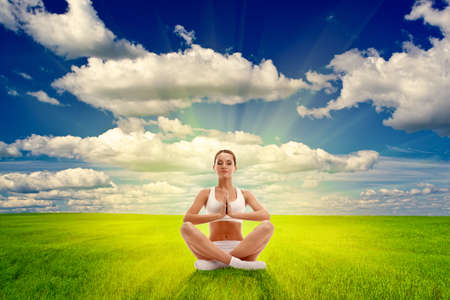 woman meditating on summer field over sunset photo