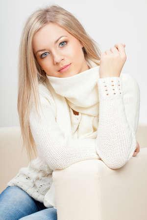 blonde Frau mit Pullover sitzt auf dem Sofa