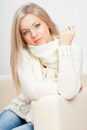 blonde woman wearing sweater sitting  on sofa photo