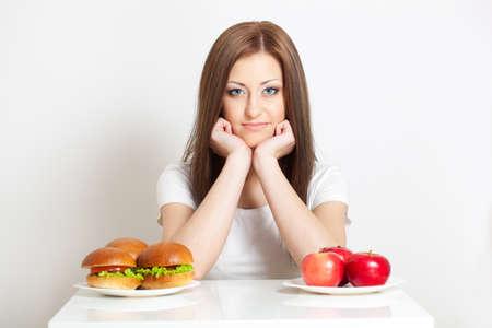 Frau sitzt hinter dem Tisch mit stehenden Junk-Food und Äpfeln