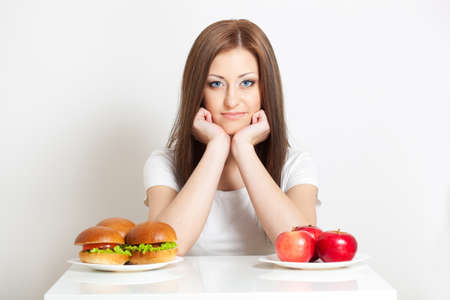 health care decisions: woman sitting behind the table with standing junk food and apples