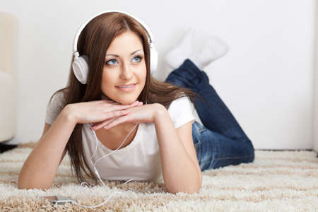 smiling brunette lying  on carpet and listen to the music photo