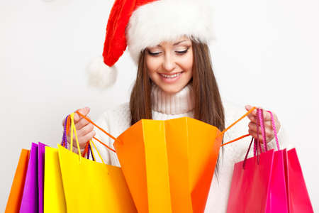 happy smiling brunette woman in santa hat holding shopping bags and looking to the bags photo