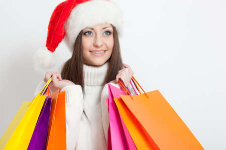 happy smiling brunette woman in santa hat holding shopping bags, copy space photo