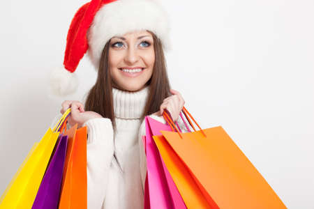 happy smiling brunette woman in santa hat holding shopping bags, copy space for text photo