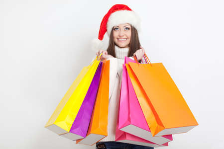 brunette woman in santa hat holding shopping bags photo