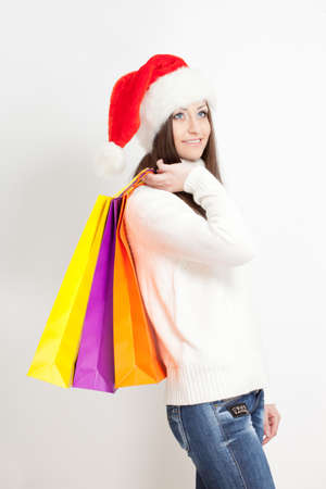 happy smiling brunette woman in santa hat holding sopping bags photo
