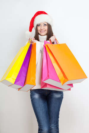 happy smiling brunette woman in santa hat holding shopping bags, vertical photo