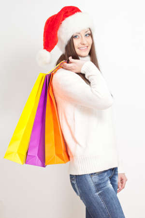 happy smiling brunette woman in santa hat holding shopping bags photo