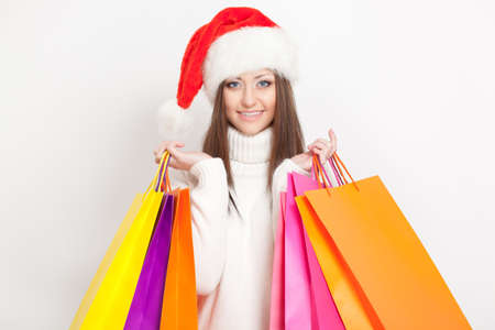 happy  brunette woman in santa hat holding shopping bags photo