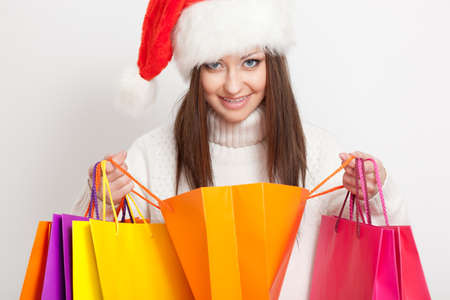 happy smiling brunette woman in santa hat holding opened shopping bags photo