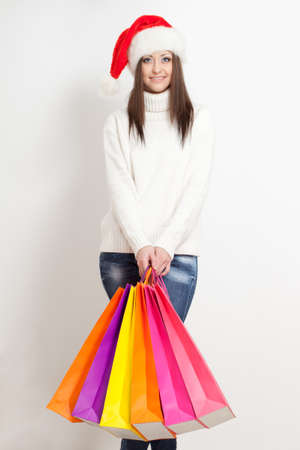 happy smiling brunette woman in santa hat holding color  shopping bags Stock Photo - 16659423