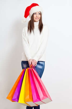 happy smiling brunette woman in santa hat holding color  shopping bags photo