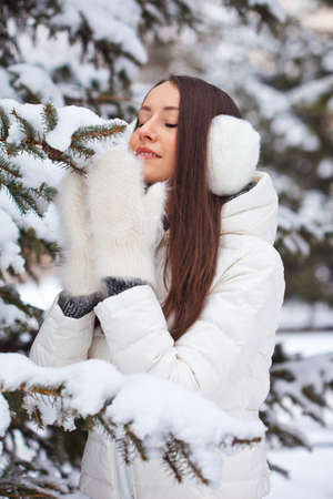 brunette woman walking in winter park and sniffing fur tree