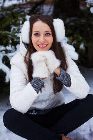 mitten: brunette woman sitting  in winter park under fur tree