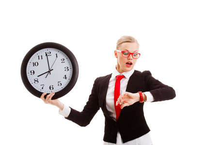 blonde businesswoman holding clock and looking to watch