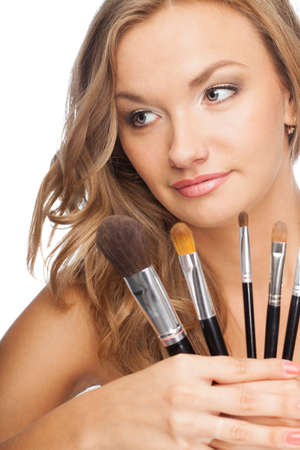 blonde woman holding set of cosmetic brushes photo
