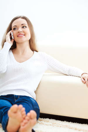 happy brunette woman sitting on carpet near sofa and talking by phone Stock Photo - 17613867