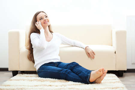 brunette woman sitting on carpet near sofa and talking by phone, horizontal Stock Photo - 17613864