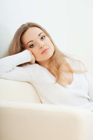 brunette  woman sitting on the sofa at room and looking at camera Stock Photo - 17606718