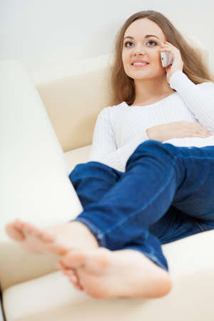 brunette woman lying on sofa and talking by cell phone, vertical Stock Photo - 17606721