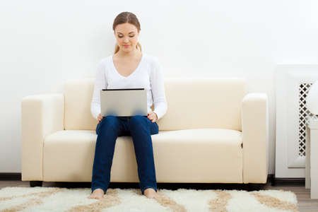 happy brunette  woman sitting on sofa with laptop Stock Photo - 17613851